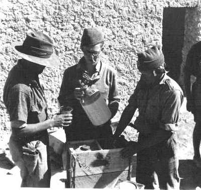 photo showing WWII british troops pouring out rum from a demijon marked S.R.D